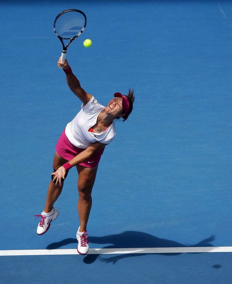 Photo - Li Na of China serves to Belinda Bencic of Switzerland during their second round match at the Australian Open tennis championship in Melbourne, Australia, Wednesday, Jan. 15, 2014.(AP Photo/Aaron Favila)