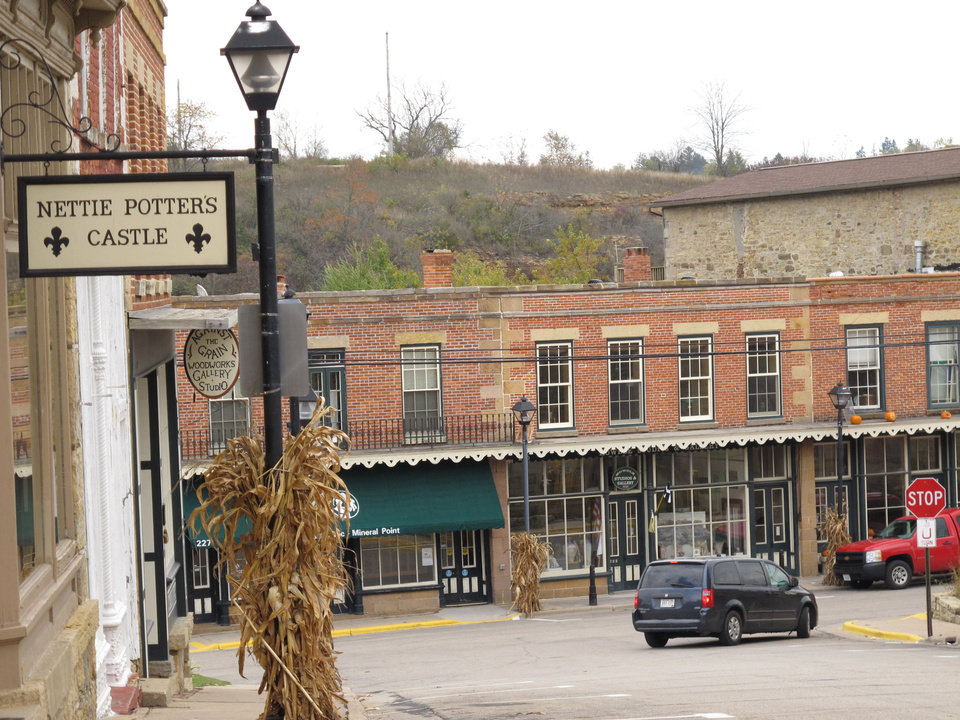 Photo - This Oct. 23, 2013 photo shows High Street in Mineral Point, Wis. The former lead mining town is a charming place of restored old limestone buildings filled with artists galleries, pottery studios and antique shops. Many of the town's 2,500 residents are artists who live above their studios. A thriving community arts center draws people from around the country to study everything from blacksmithing and bent twig furniture to poetry and the Cornish language. (AP Photo/Helen O'Neill)