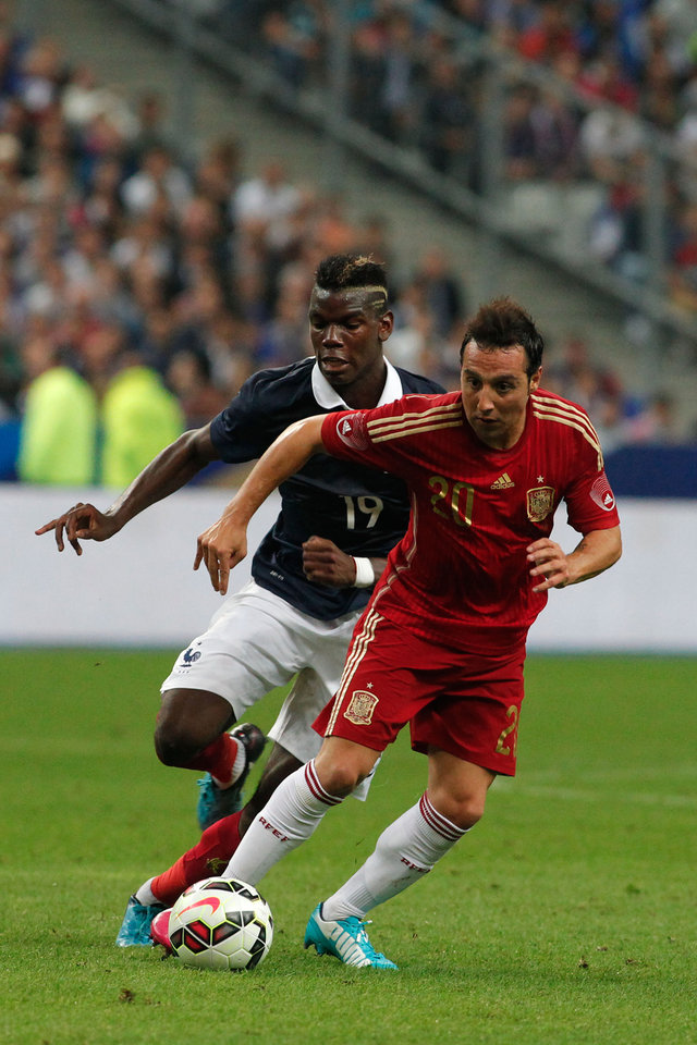 Photo - Spain's Santi Cazorla, right, vies for the ball with France's Paul Pogba during their international friendly soccer match at the Stade de France in Saint Denis, outside Paris, Thursday, Sept. 4, 2014. (AP Photo/Thibault Camus)