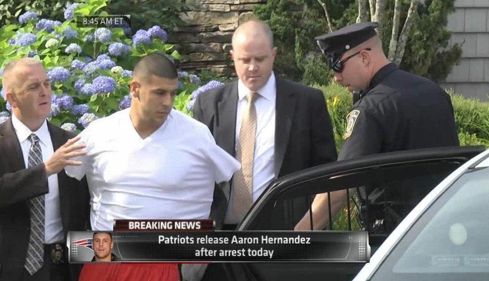 Photo - In this image taken from video, police escort Aaron Hernandez from his home in handcuffs in Attleboro, Mass., Wednesday, June 26, 2013. Hernandez was taken from his home more than a week after a Boston semi-pro football player was found dead in an industrial park a mile from Hernandez's house. (AP Photo/ESPN)
