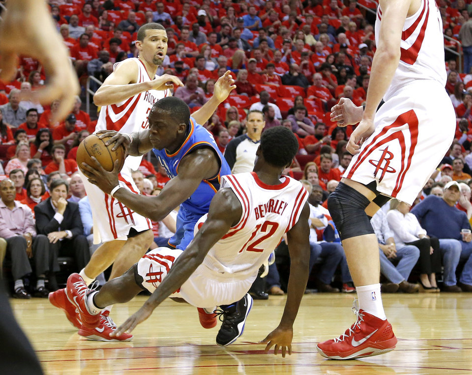 Photo - Oklahoma City's Reggie Jackson (15) falls down between Houston's Francisco Garcia (32) and Patrick Beverley (12) during Game 4 in the first round of the NBA playoffs between the Oklahoma City Thunder and the Houston Rockets at the Toyota Center in Houston, Texas,Sunday, April 29, 2013. Photo by Bryan Terry, The Oklahoman