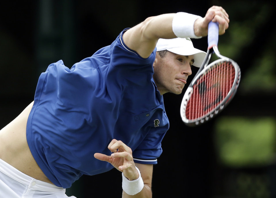 Photo - John Isner of the USA serves to opponent Ivo Karlovic of Croatia during a quarterfinal match at the Hall of Fame Tennis Championships in Newport, R.I. Friday, July 12, 2013. Isner won 7-6 (3), 7-6 (3). (AP Photo/Elise Amendola)