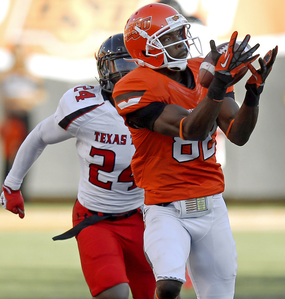 Photo - Oklahoma State's Isaiah Anderson (82) catches a touchdown pass in front of Texas Tech's Bruce Jones (24) during a college football game between Oklahoma State University (OSU) and Texas Tech University (TTU) at Boone Pickens Stadium in Stillwater, Okla., Saturday, Nov. 17, 2012.  Photo by Bryan Terry, The Oklahoman