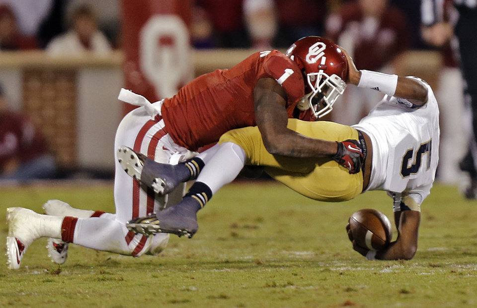 Photo - OU's Tony Jefferson (1) brings down Notre Dame 's Everett Golson (5) during the college football game between the University of Oklahoma Sooners (OU) and the Notre Dame Fighting Irish at the Gaylord Family-Oklahoma Memorial Stadium on Saturday, Oct. 27, 2012, in Norman, Okla. Photo by Chris Landsberger, The Oklahoman