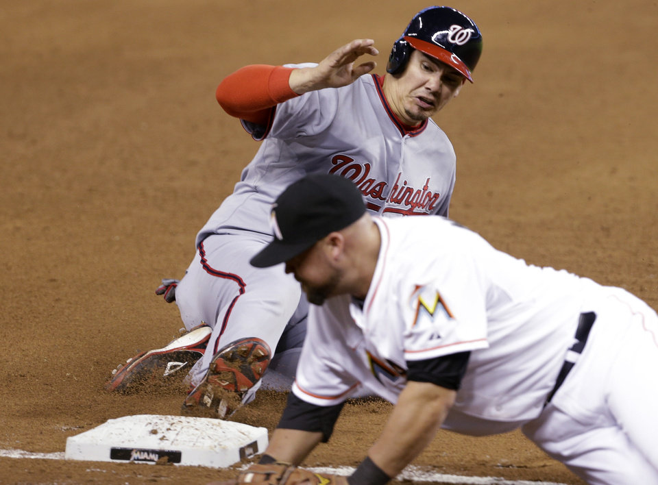 Photo - Washington Nationals' Jose Lobaton, left, is safe at third base on a throwing error by Miami Marlins catcher Jarrod Saltalamacchia during the sixth inning of a baseball game, Wednesday, April 16, 2014, in Miami. At right is Miami Marlins third baseman Casey McGehee. (AP Photo/Lynne Sladky)