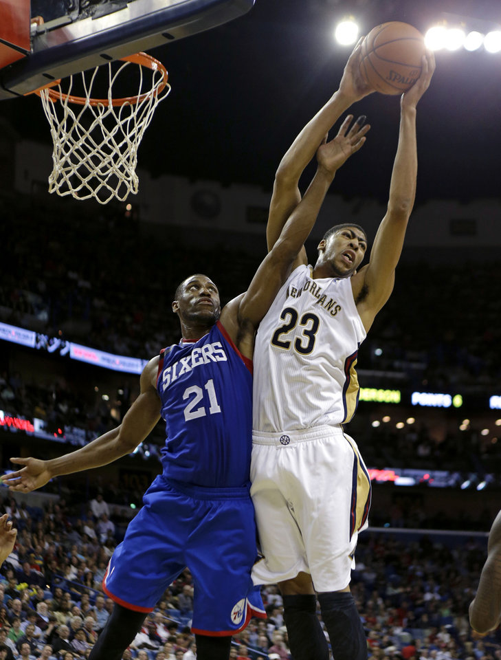 Photo - New Orleans Pelicans power forward Anthony Davis (23) grabs a rebound over Philadelphia 76ers power forward Thaddeus Young (21) in the first half of an NBA basketball game in New Orleans, Saturday, Nov. 16, 2013. (AP Photo/Gerald Herbert)