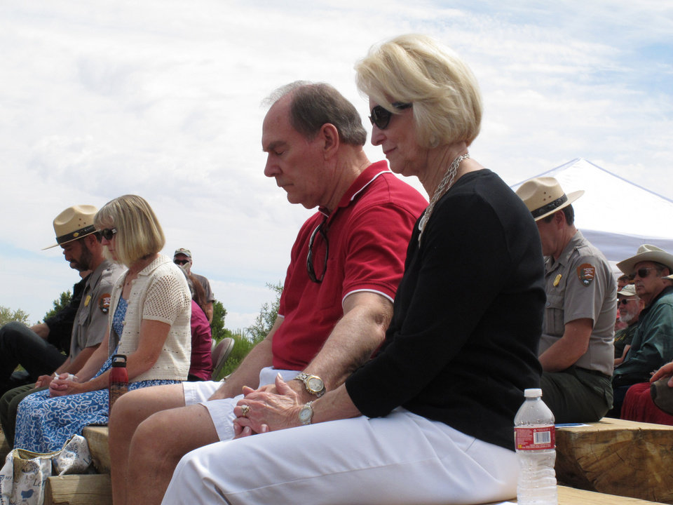 Photo - Christa Cook, right, and her husband, Ray Cook, bow their heads to remember those aboard two commercial airliners that collided mid-air over the Grand Canyon in Arizona in 1956. Grand Canyon National Park unveiled a plaque, Tuesday, July 8, 2014, that designates the crash site as a National Historic Landmark. Ray Cook's father was among the 128 killed. (AP Photo/Felicia Fonseca)