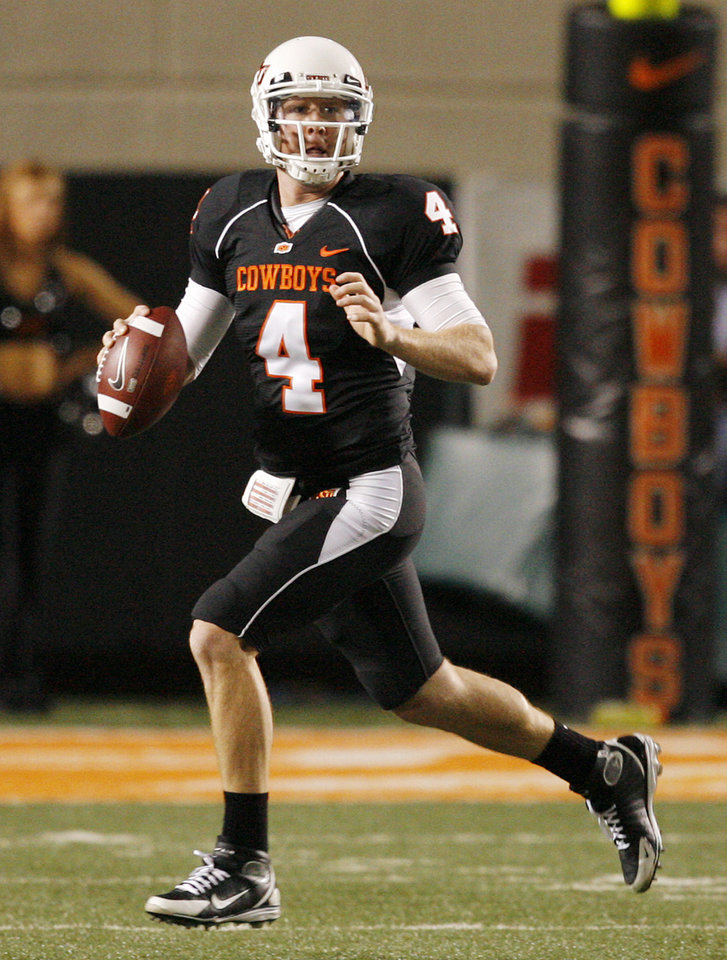 Photo - OSU's Brandon Weeden (4) looks for a receiver during the college football game between Oklahoma State University (OSU) and the University of Colorado (CU) at Boone Pickens Stadium in Stillwater, Okla., Thursday, Nov. 19, 2009. OSU won, 31-28. Photo by Nate Billings, The Oklahoman