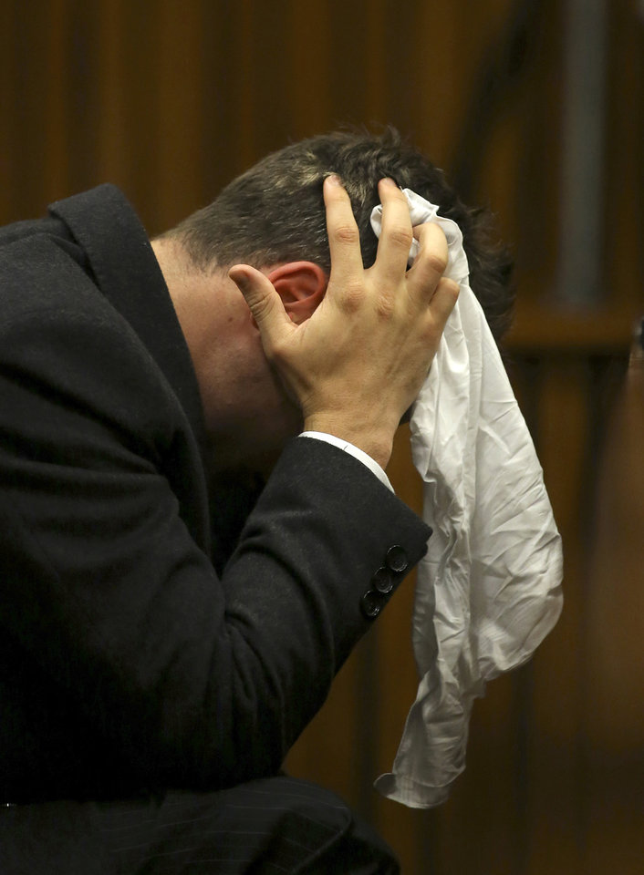 Photo - Oscar Pistorius covers his head with a handkerchief after he had reached for a bucket at his feet while listening to cross questioning about the events surrounding the shooting death of his girlfriend Reeva Steenkamp, in his second week in court during his trial in Pretoria, South Africa, Monday, March 10, 2014. Pistorius is charged with the shooting death of his girlfriend  Steenkamp, on Valentines Day in 2013. (AP Photo/Siphiwe Sibeko, Pool)