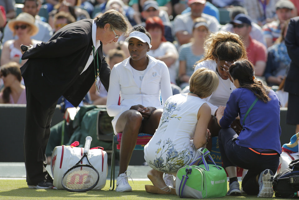 Photo - Court officials talk to Serena Williams and Venus Williams, left, of the U.S as they retire after 3 games from their women's doubles match against Kristina Barrois of Germany and Stefanie Voegele of Switzerland at the All England Lawn Tennis Championships in Wimbledon, London, Tuesday July 1, 2014. (AP Photo/Pavel Golovkin)