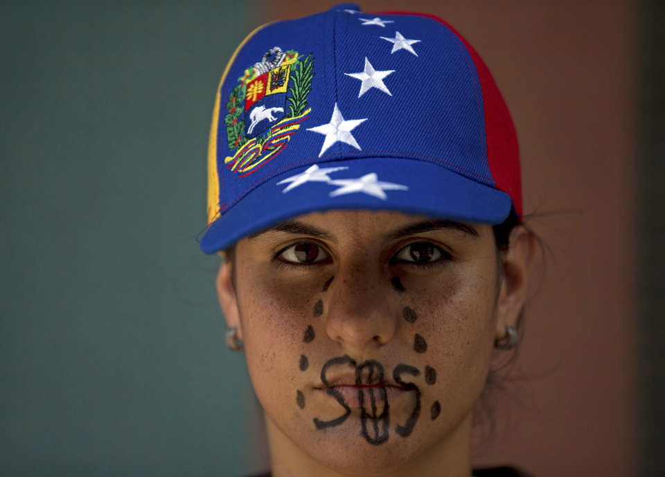 Photo - A woman wearing a cap representing Venezuela's national flag, the SOS distress signal marked across her lips and painted black tears streaming down her face, looks into the camera during a demonstration in Caracas, Venezuela, Saturday, March 8, 2014. Venezuelans returned to the streets for the