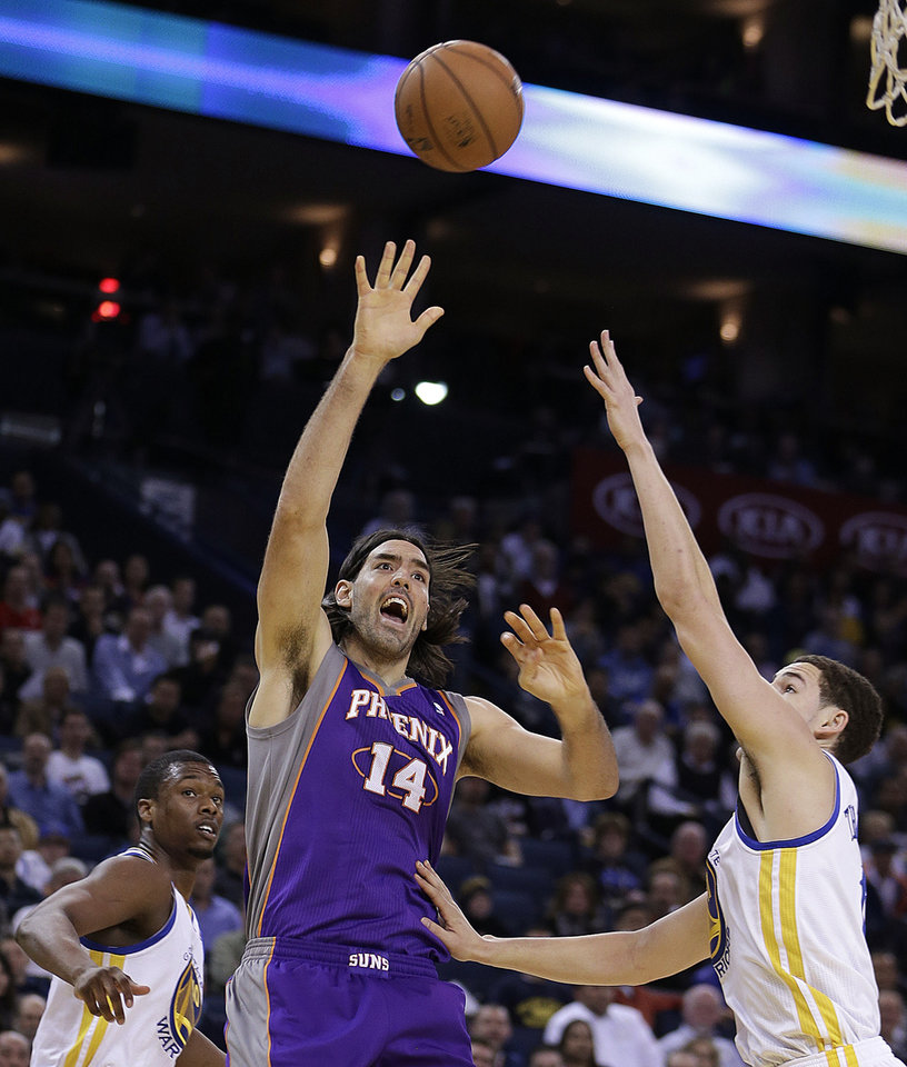Phoenix Sun's Luis Scola (14) shoots against Golden State Warriors' Klay Thompson, right, during the first half of an NBA basketball game Wednesday, Feb. 20, 2013, in Oakland, Calif. (AP Photo/Ben Margot)