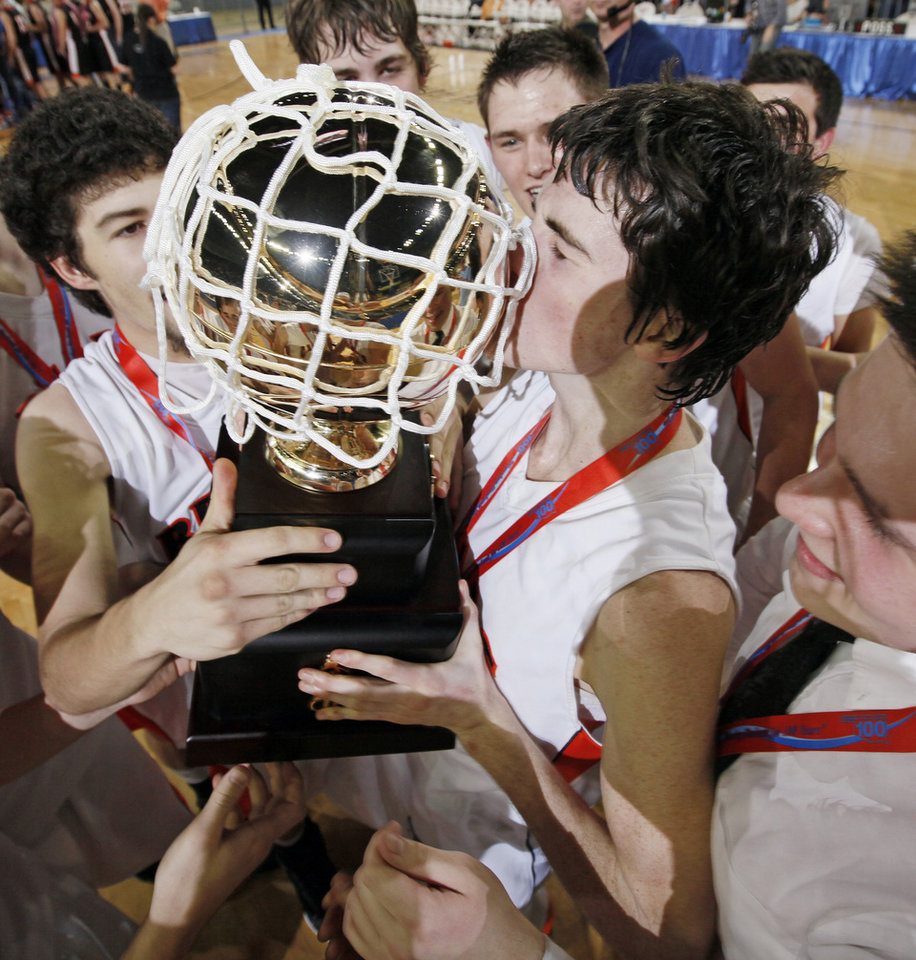 Photo - Cheyenne-Reydon's Austin Thrash (12), right, kisses the gold ball championship trophy after the Class A boys state championship high school basketball game between Cheyenne-Reydon and Merritt at State Fair Arena in Oklahoma City, Saturday, March 3, 2012. Cheyenne-Reydon won, 51-30. Photo by Nate Billings, The Oklahoman