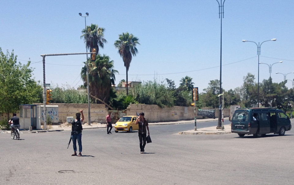 Photo - A fighter, center left, with the al-Qaida-inspired Islamic State of Iraq and the Levant (ISIL) takes control of a traffic intersection in the northern city of Mosul, 225 miles (360 kilometers) northwest of Baghdad, Iraq, Sunday, June 22, 2014. Sunni militants on Sunday captured two border crossings, one along the frontier with Jordan and the other with Syria, security and military officials said, as they pressed on with their offensive in one of Iraq's most restive regions. (AP Photo)