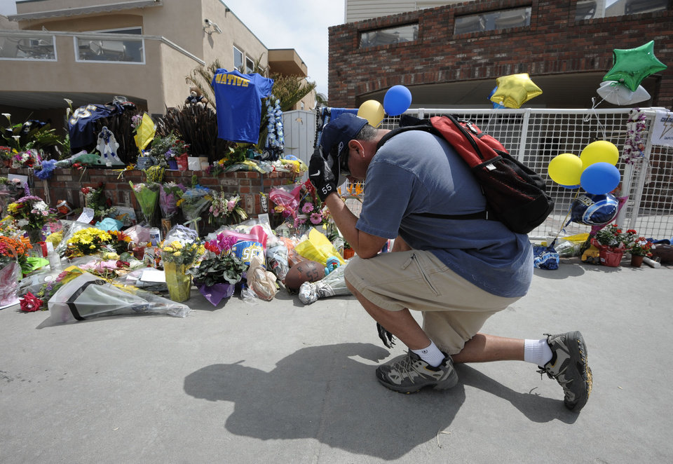 Photo -   San Diego Chargers fan Dennis Telles bows down in front of a memorial in the driveway of the house of former NFL star Junior Seau Thursday, May 3, 2012, in Oceanside, Calif. Seau's death stunned the region he represented with almost reckless abandon. (AP Photo/Denis Poroy)