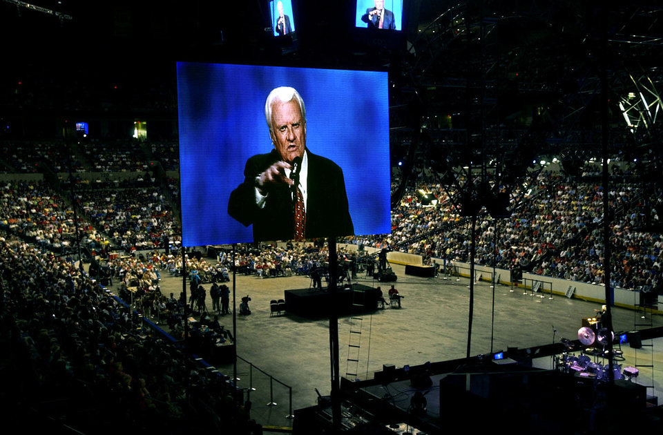 Photo - The Rev. Billy Graham is seen on a large screen TV over a crowd of 29,000 at the then-Ford Center during the Mission Oklahoma City in 2003, the last time the renowned evangelist led a faith outreach effort in Oklahoma.  BRYAN TERRY