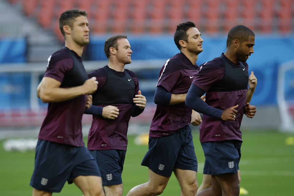 Photo - England's, from left, Gary Cahill, Wayne Rooney, Frank Lampard, and Glen Johnson jog during a training session of the England national soccer team at the Arena da Amazonia in Manaus, Brazil, Friday, June 13, 2014.  England play Italy in group D of the 2014 soccer World Cup at the stadium on Saturday.  (AP Photo/Matt Dunham)