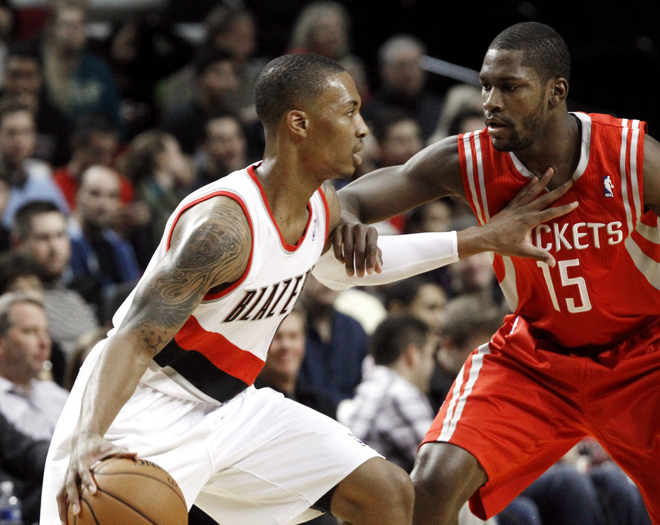Portland Trail Blazers guard Damian Lillard, left, works the ball against Houston Rockets guard Toney Douglas during the first half of their NBA basketball game in Portland, Ore., Friday, Nov. 16, 2012. (AP Photo/Don Ryan)