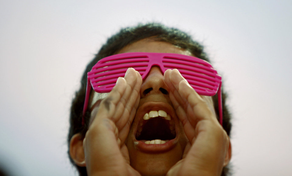 Photo - Wearing pink glasses for Win-Win Week to raise cancer awareness, Moore freshman Kyle Hoffman, 15, cheers during the high school football game between Moore and Southmoore on Thursday, September 17, 2010.  Photo by Bryan Terry, The Oklahoman