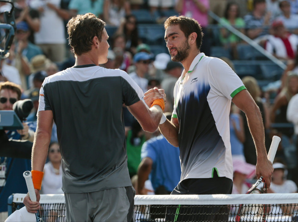 Photo - Marin Cilic, of Croatia, right, greets Tomas Berdych, of the Czech Republic, at the net after winning their quarterfinal match of the 2014 U.S. Open tennis tournament, Thursday, Sept. 4, 2014, in New York. (AP Photo/Julio Cortez)