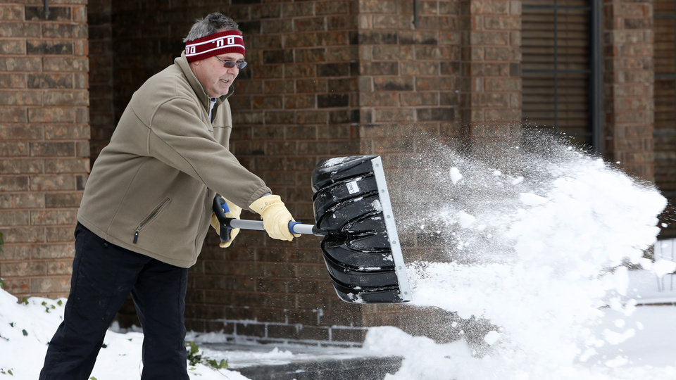 Barry Wilson shovels snow from his sidewalk on Steve Court in Yukon, Thursday December 6, 2013. Photo By Steve Gooch, The Oklahoman