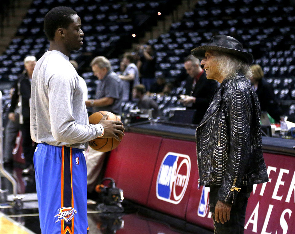 Photo - Oklahoma City's Reggie Jackson (15) talks with NBA fan James Goldstein before Game 1 of the Western Conference Finals in the NBA playoffs between the Oklahoma City Thunder and the San Antonio Spurs at the AT&T Center in San Antonio, Monday, May 19, 2014. Photo by Sarah Phipps, The Oklahoman