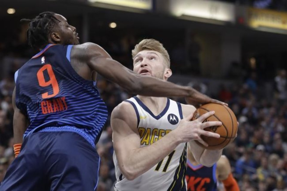 Photo -  Indiana's' Domantas Sabonis, right, puts up a shot against Oklahoma City's Jerami Grant during the second half of Thursday's game in Indianapolis. Sabonis, a former Thunder player, hit two critical free throws late in the Pacers' 108-106 comeback win. [AP Photo/Darron Cummings]
