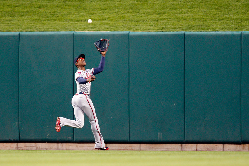 Photo - Atlanta Braves center fielder B.J. Upton goes after but is unable to catch a deep fly ball hit by St. Louis Cardinals' Allen Craig resulting in an RBI double during the second inning of a baseball game Friday, May 16, 2014, in St. Louis. (AP Photo/Scott Kane)