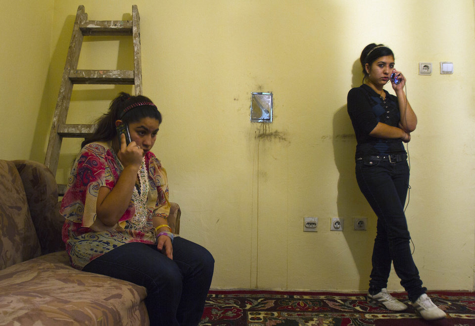 Photo - Leonarda 15, left, and Maria Dibrani 17, expelled from France last week, talk on their mobile phones in a shelter house in Mitrovica, northern Kosovo, Wednesday, Oct 16, 2013. France's government, trying to save face amid widespread outrage, said Wednesday that it is investigating the treatment of a 15-year-old girl of the Dibrani family who was detained by police in front of her fellow students so she and her family could be expelled to Kosovo as illegal immigrants. (AP Photo/Visar Kryeziu)