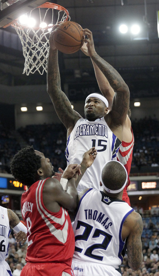 Photo - Sacramento Kings center DeMarcus Cousins, (15) grabs a rebound over Houston Rockets guard Patrick Beverley, left, and Kings guard Isaiah Thomas during the first quarter of an NBA basketball game in Sacramento, Calif., Tuesday Feb. 25, 2014. (AP Photo/Rich Pedroncelli)