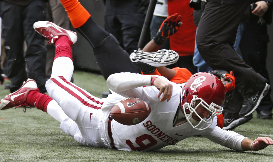 Photo - Oklahoma's Trevor Knight (9) hits the turf that had him leave the game holding his wrist before half time during the Bedlam college football game between the Oklahoma State University Cowboys (OSU) and the University of Oklahoma Sooners (OU) at Boone Pickens Stadium in Stillwater, Okla., Saturday, Dec. 7, 2013. Photo by Chris Landsberger, The Oklahoman