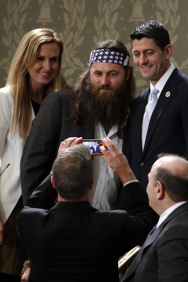 Photo - Duck Dynasty's Willie Robertson, center and his wife Korie, pose with Rep. Paul Ryan, R-Wis., before President Barack Obama's State of the Union address on Capitol Hill in Washington, Tuesday Jan. 28, 2014. (AP Photo/Charles Dharapak)