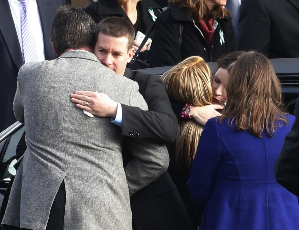 Richard Rekos and Krista Rekos, with faces shown, parents of Jessica Rekos, are hugged by mourners outside of St. Rose of Lima Roman Catholic Church after funeral services, Tuesday, Dec. 18, 2012, in Newtown, Conn. Jessica Rekos, 6, was killed when Adam Lanza walked into Sandy Hook Elementary School in Newtown, Conn., Dec. 14, and opened fire, killing 26 people, including 20 children, before killing himself. (AP Photo/Julio Cortez) ORG XMIT: CTJC125