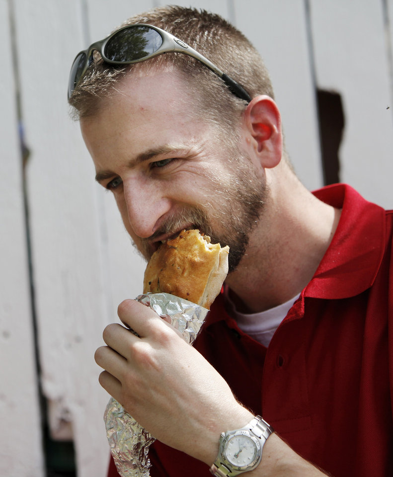 Photo - Mark McCormick eats an All Meat Calzone from  the Sammy's Pizza & Prairie Dance Theatre booth on International Food Row during the Festival of the Arts in downtown Oklahoma City, Wednesday, April 25, 2012. Photo by Nate Billings, The Oklahoman