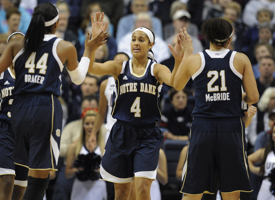 Notre Dame's Skylar Diggins (4) high-fives teammates Ariel Braker (44) and Kayla McBride (21) during the first half of an NCAA college basketball game against Connecticut in Storrs, Conn., Saturday, Jan. 5, 2013. (AP Photo/Jessica Hill)