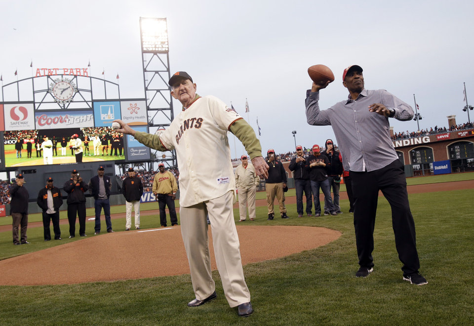 Photo - Former San Francisco Giants manager Roger Craig, left, and Former San Francisco 49ers' Keena Turner throw out ceremonial first pitches before a baseball game between the Giants and the Arizona Diamondbacks, Thursday, April 10, 2014, in San Francisco. (AP Photo/Marcio Jose Sanchez)