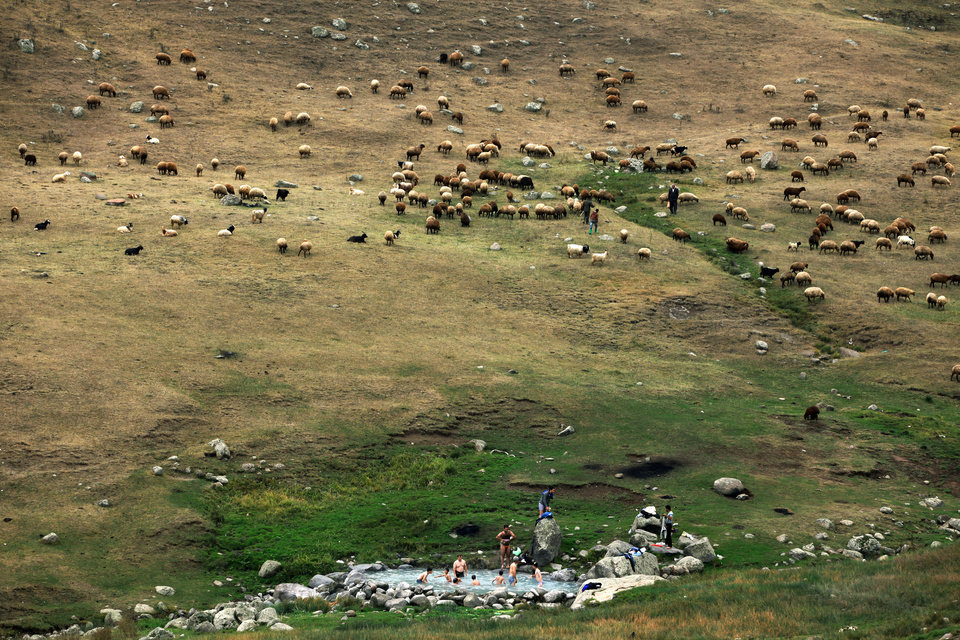 Photo - In this Sept. 13, 2013 photo, Iranians bathe at a hot mineral water spring on the slopes of Iran's Sabalan mountain, in the northwestern town of Sarein. Animals graze on grassy hillsides in the background. (AP Photo/Ebrahim Noroozi)