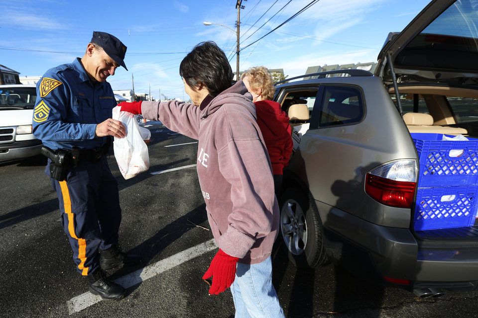 Photo - Anne Amodio, center, and Lynn Corino, right, hand a bag of food to New Jersey State Police Sgt. Schafer as members of St. Mary's by the Sea drove around to feed first responders working at Point Pleasant Beach following Superstorm Sandy, Thursday, Nov. 8, 2012, in Point Pleasant, N.J. (AP Photo/Julio Cortez) ORG XMIT: NJJC124