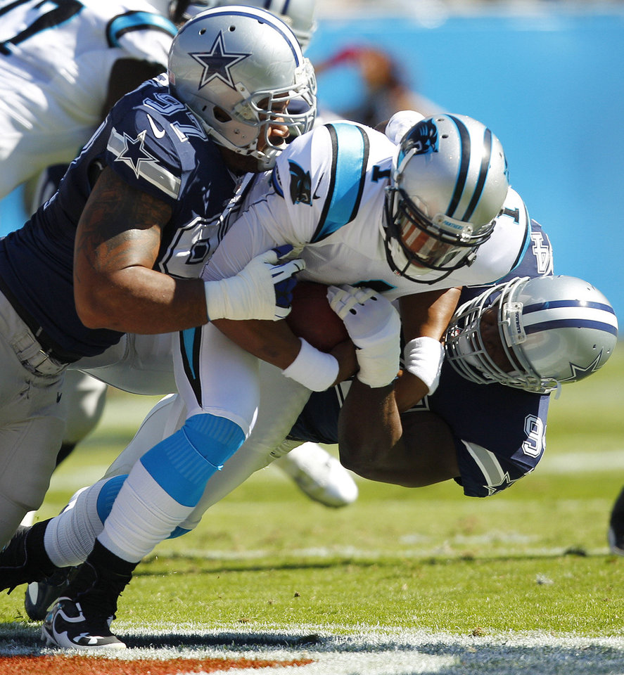 Photo -   Dallas Cowboys defensive end Jason Hatcher (97) and Dallas Cowboys outside linebacker DeMarcus Ware (94) sack Carolina Panthers quarterback Cam Newton (1) during the first half of an NFL football game, Sunday, Oct. 21, 2012, in Charlotte. (AP Photo/Chuck Burton)