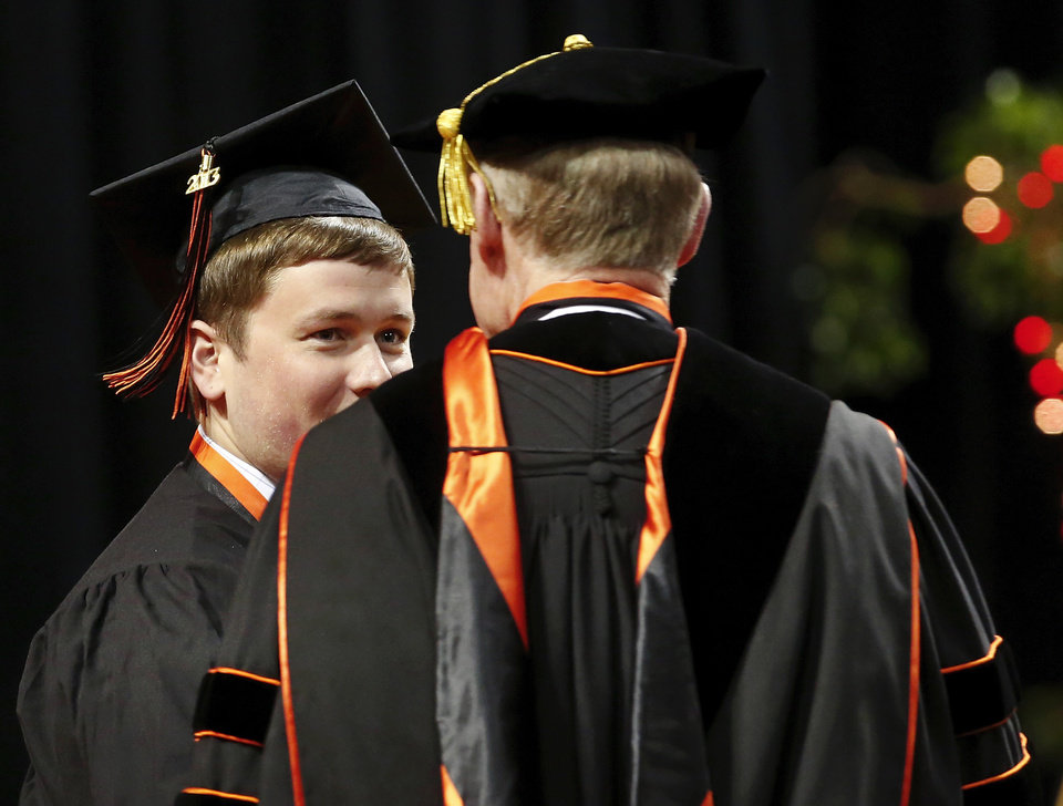 A graduate is congratulated by OSU President Burns Hargis as he walks across the stage after receiving his diploma.  Undergraduates at OSU participated in the school's 127th commencement ceremony the weekend of Friday, May 3 and Saturday, May 4, 2013 inside Gallagher-Iba Arena on the university's campus.These photos were taken at the Saturday morning ceremony when students from the College of Agricultural Sciences and Natural Resources, and the Spears School of Business were conferred with degrees.   Photo  by Jim Beckel, The Oklahoman.