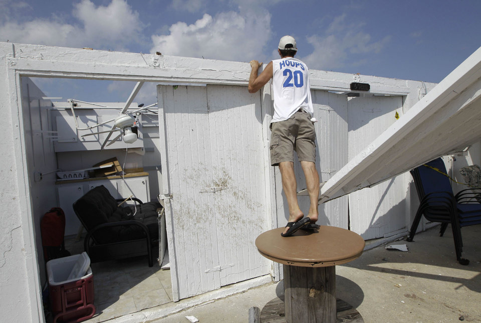 Photo -   Cabana owner Bill Ryan looks into other roofless cabanas at the Breezy Point Surf Club in New York, Saturday, Sept. 8, 2012, after a possible tornado touched down in the area during severe weather. Ryan's cabana also lost it's roof in the storm. A tornado swept out of the sea and hit the beachfront neighborhood in New York City, hurling debris in the air, knocking out power and startling residents who once thought of twisters as a Midwestern phenomenon. Firefighters were still assessing the damage, but no serious injuries were reported and the area affected by the storm appeared small.(AP Photo/Kathy Willens)