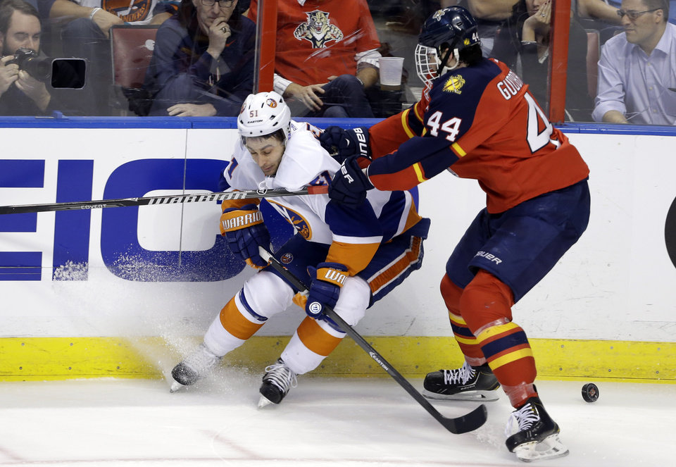 Photo - New York Islanders' Frans Nielsen (51) and Florida Panthers' Erik Gudbranson (44) go for the puck during the first period of an NHL hockey game, Tuesday, Jan. 14, 2014, in Sunrise, Fla. (AP Photo/Lynne Sladky)