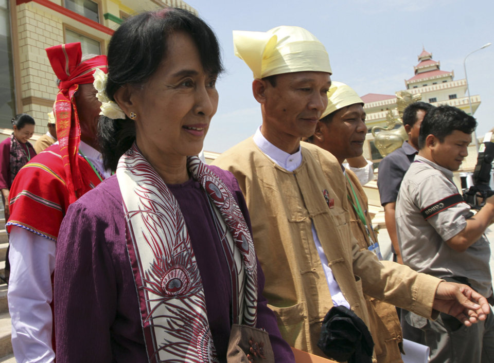 Photo -   Opposition leader Aung San Suu Kyi, left, leaves the parliament building after attending a regular session of Myanmar Lower House, in Naypyitaw, Myanmar, Wednesday, May 2, 2012. Suu Kyi was set to be sworn in to Myanmar's military-backed parliament Wednesday to take public office for the first time since launching her struggle against authoritarian rule nearly a quarter century ago. (AP Photo/Khin Maung Win)