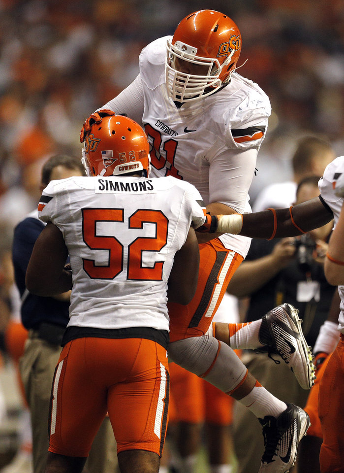 Photo - Oklahoma State's James Castleman (91) and Ryan Simmons (52) celebrate a Simmons interception during the second half of a college football game between the University of Texas at San Antonio Roadrunners (UTSA) and the Oklahoma State University Cowboys (OSU) at the Alamodome in San Antonio, Saturday, Sept. 7, 2013.  Photo by Sarah Phipps, The Oklahoman