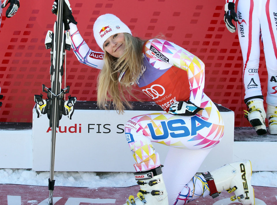 FILE - In this Dec. 7, 2011 file photo, Lindsey Vonn kneels down in front of the podium after winning the women's World Cup Super G  ski competition in Beaver Creek, Colo. Vonn was supposed to make her World Cup return this week on a course almost custom-made for her. But after re-injuring her knee last week, the four-time World Cup champ is sitting this one out. (AP Photo/Alessandro Trovati, File)
