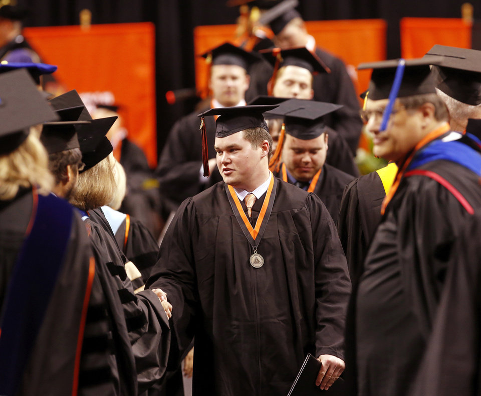 Graduates are congratulated by university faculty representatives as they return to their seats after walking across the stage. Undergraduates at OSU participated in the school\'s 127th commencement ceremony the weekend of Friday, May 3 and Saturday, May 4, 2013 inside Gallagher-Iba Arena on the university\'s campus.These photos were taken at the Saturday morning ceremony when students from the College of Agricultural Sciences and Natural Resources, and the Spears School of Business were conferred with degrees. Photo by Jim Beckel, The Oklahoman.