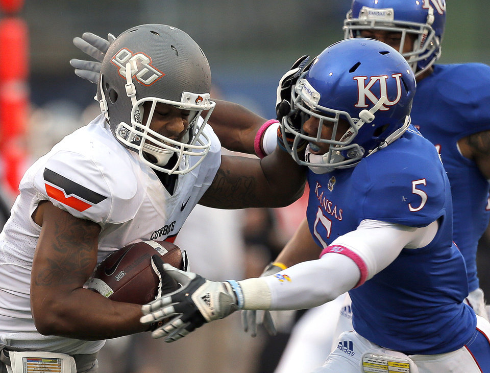 Oklahoma State's Tracy Moore (87) tries to get by Kansas' Greg Brown (5) during the college football game between Oklahoma State University (OSU) and the University of Kansas (KU) at Memorial Stadium in Lawrence, Kan., Saturday, Oct. 13, 2012. Photo by Sarah Phipps, The Oklahoman