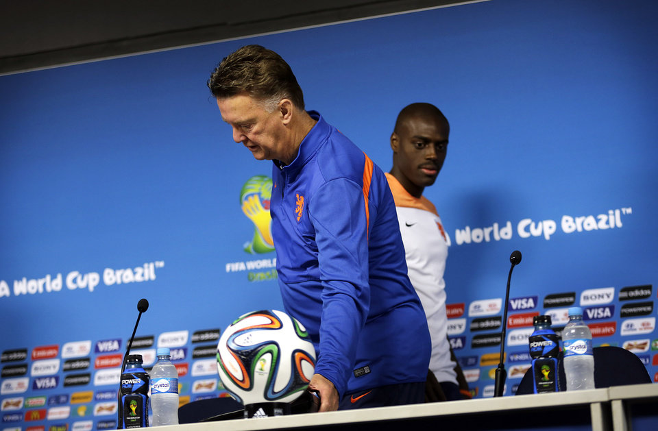 Photo - Bruno Martins Indi, right, walks past his coach Louis van Gaal, left, of the Netherlands as they arrive for a press conference at the Itaquerao Stadium in Sao Paulo, Brazil, Sunday, June 22, 2014.  The Netherlands will play Chile in a match that will decide the winner of Group B at the 2014 soccer World Cup. (AP Photo/Wong Maye-E)