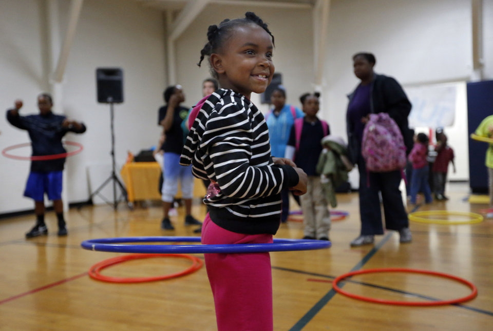 Photo - Jaionna Harris, 6, hula hoops during YMCA Healthy Kids Day at the Northside YMCA on Tuesday. Photo by Sarah Phipps, The Oklahoman  SARAH PHIPPS - SARAH PHIPPS