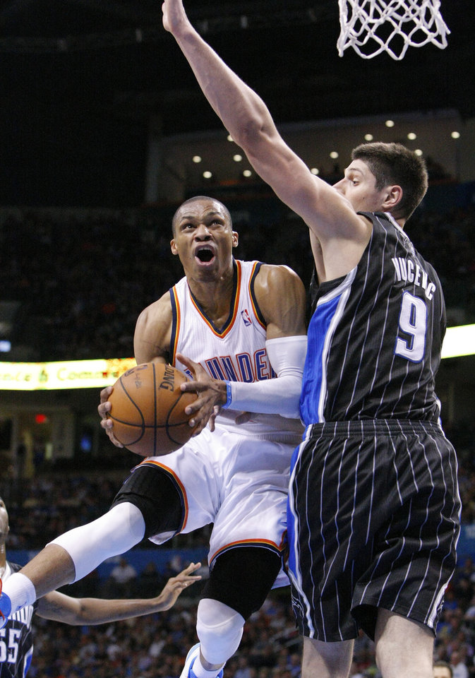 Oklahoma City Thunder guard Russell Westbrook, left, goes to the basket around Orlando Magic center Nikola Vucevic, right, during the third quarter of an NBA basketball game in Oklahoma City, Friday, March 15, 2013. Oklahoma City won 117-104. (AP Photo/Alonzo Adams)